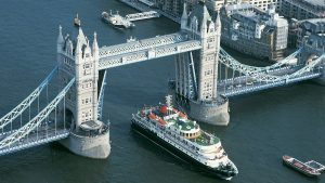 Aerial photograph of ocean liner or yacht passing through Tower Bridge in London