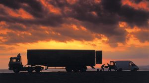 Commercial transport company atmospheric photography with lorry and van transfer under Morecambe Bay sunset.