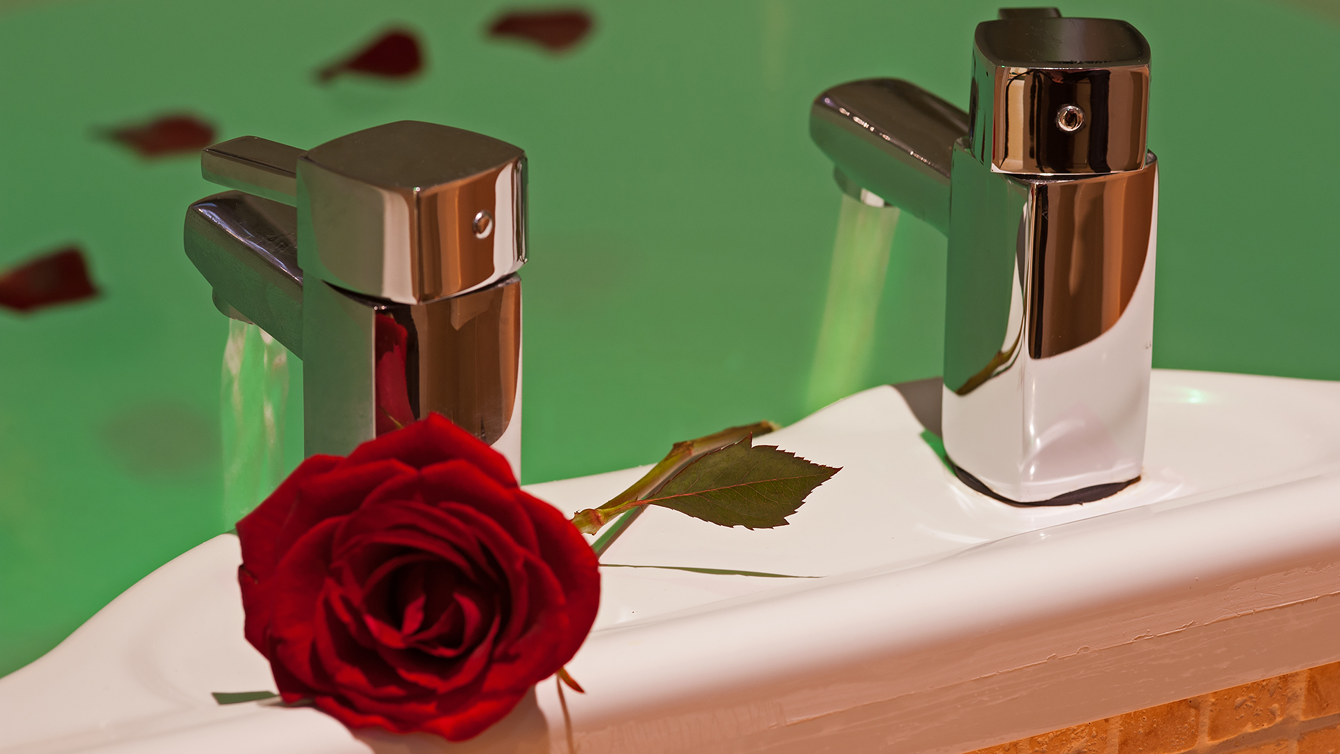 Bathroom Detail Showing gold plate effect taps and red rose